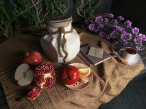 Tarro, manzanas, granada, taza del coffe con los libros y naranja en aún-vida conceptual de la pañería de la lona Fotografía de archivo libre de regalías