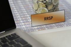 Tarro por completo de las monedas para RRSP en la hoja de cálculo al lado del ordenador portátil fotos de archivo libres de regalías