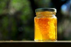 Tarro retroiluminado de miel con el panal en la madera Fotografía de archivo