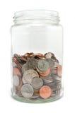 Tarro semilleno de monedas Fotos de archivo