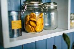 Tarro transparente de galletas en el estante de madera en la cocina foto de archivo libre de regalías