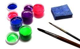 Tarros con diversas pinturas acrílicas del color, los cepillos y una esponja t Imagen de archivo libre de regalías