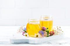 Tarros con la miel de la flor en el fondo de madera blanco Fotografía de archivo libre de regalías