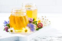 tarros con la miel de la flor en el fondo de madera blanco, primer Imagen de archivo libre de regalías