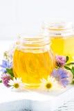tarros con la miel de la flor fresca en el fondo blanco, vertical Imágenes de archivo libres de regalías