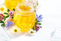 tarros con la miel de la flor fresca en el fondo blanco, visión superior Foto de archivo