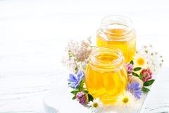 Tarros con la miel de la flor fresca en el tablero blanco Foto de archivo