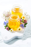 Tarros con la miel de la flor fresca en el tablero blanco, vertical Fotos de archivo libres de regalías
