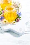 Tarros con la miel de la flor fresca en el tablero de madera blanco, vertical Imágenes de archivo libres de regalías