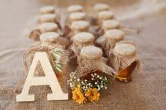 Tarros con la miel y las flores anaranjadas en un fondo de despido Fotografía de archivo