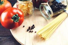 Tarros con las especias, los tomates y las pastas Foto de archivo libre de regalías