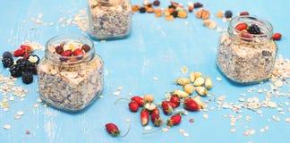 Tarros con muesli, las bayas, las nueces y las semillas en backgro rústico azul Imagen de archivo libre de regalías