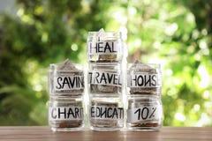 Tarros de cristal con el dinero para diversas necesidades en la tabla fotos de archivo libres de regalías