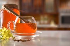 Tarros de cristal con la miel en la vista delantera blanca de la tabla de cocina Imagenes de archivo