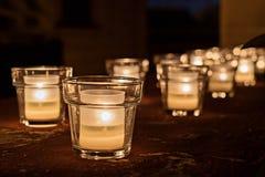 Tarros de cristal con las velas ardientes en la oscuridad foto de archivo libre de regalías