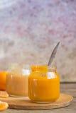 Tarros de cristal con los alimentos para niños naturales en la tabla de madera Imagen de archivo