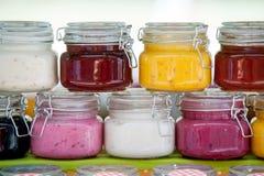 Tarros de cristal con los atascos coloridos en fila imagen de archivo libre de regalías