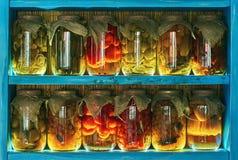 Tarros de cristal cubiertos con la tela de la arpillera con diversa comida enlatada hecha en casa, verduras preservadas en estant foto de archivo libre de regalías