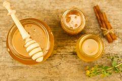 Tarros de cristal de miel fresca con el drizzler, canela, flores en el fondo de madera, visión superior Imagen de archivo