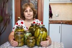 Tarros de cristal del abarcamiento maduro de la mujer con los pepinos adobados mientras que se sienta en propia cocina nacional Fotografía de archivo libre de regalías