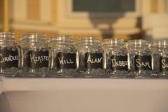 Tarros de cristal del tablero de tiza con nombres Foto de archivo