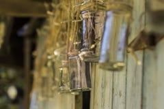 Tarros de cristal que cuelgan de secuencia fuera de una vertiente analizada foto de archivo libre de regalías