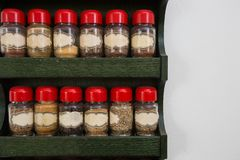Tarros de hierbas y de especias en estante de madera en el fondo blanco, dise?o del vintage fotografía de archivo