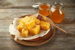 Tarros de la miel y de la placa dulces con los peines Imagenes de archivo