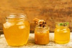 Tarros de miel con canela, flores en fondo de madera Imagen de archivo