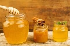 Tarros de miel con el drizzler, canela, flores en fondo de madera Imagenes de archivo