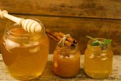 Tarros de miel con el drizzler, canela, flores en fondo de madera Imágenes de archivo libres de regalías