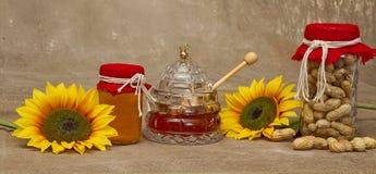 Tarros de miel y de cacahuetes con los girasoles Fotos de archivo
