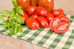 Tarros de salsa con los tomates y la albahaca de la goma Fotografía de archivo