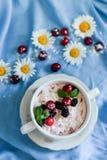 Tarros de yogur blanco natural con la ensalada de fruta con la fruta, las bayas y la menta rosadas del drag?n en la tabla Consumi fotos de archivo libres de regalías