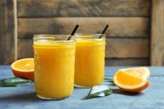 Tarros de zumo de naranja y de frutas frescas Foto de archivo libre de regalías