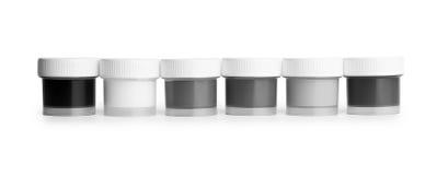 Tarros descolorados de la gama de colores de la gouache en una fila Imagenes de archivo