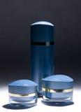 Tarros y botella poner crema azules Fotos de archivo
