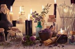 Tarros y botellas de cristal con las velas negras y las hierbas curativas en la tabla alquímica Imagenes de archivo