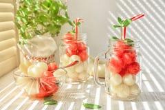 Tarros y cuenco con las bolas deliciosas del melón y de la sandía imágenes de archivo libres de regalías