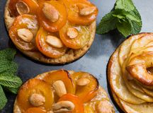 Tart with apricot and apple. Traditional french pie with fruits on dark marble background. Decorated almonds and mint. Leafs. Delicious dessert with copy space Stock Image