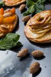Tart with apricot and apple. Traditional french pie with fruits on dark marble background. Decorated almonds and mint. Leafs. Delicious dessert with copy space Royalty Free Stock Photo
