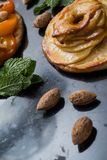Tart with apricot and apple. Traditional french pie with fruits on dark marble background. Decorated almonds and mint. Leafs. Delicious dessert with copy space Royalty Free Stock Image