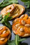 Tart with apricot and apple. Traditional french pie with fruits on dark marble background. Decorated almonds and mint. Leafs. Delicious dessert with copy space Royalty Free Stock Photography