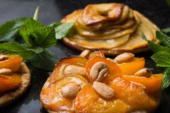 Tart with apricot and apple. Traditional french pie with fruits on dark marble background. Decorated almonds and mint. Leafs. Delicious dessert with copy space Stock Photo