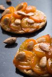 Tart with apricot and apple. Traditional french pie with fruits on dark marble background. Decorated almonds and mint Royalty Free Stock Photography