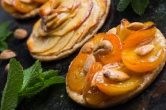 Tart with apricot and apple. Traditional french pie with fruits on dark marble background. Decorated almonds and mint Stock Photo