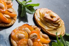 Tart with apricot and apple. Traditional french pie with fruits on dark marble background. Decorated almonds and mint Royalty Free Stock Photo