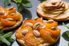 Tart with apricot and apple. Traditional french pie with fruits on dark marble background. Decorated almonds and mint. Leafs. Delicious dessert with copy space Royalty Free Stock Photos
