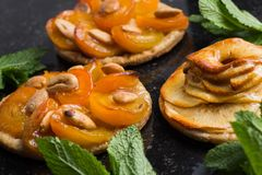 Tart with apricot and apple. Traditional french pie with fruits on dark marble background. Decorated almonds and mint. Leafs. Delicious dessert with copy space Stock Photos