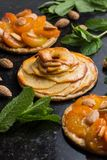 Tart with apricot and apple. Traditional french pie with fruits on dark marble background. Decorated almonds and mint. Leafs. Delicious dessert with copy space Royalty Free Stock Images